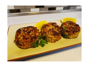 Three mile-high crab cakes on a tray next to a lemon.