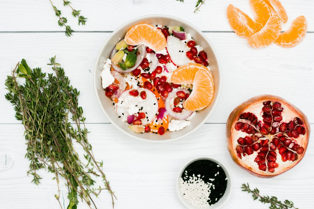 Meatless bowls of fruits on a white wooden table.
