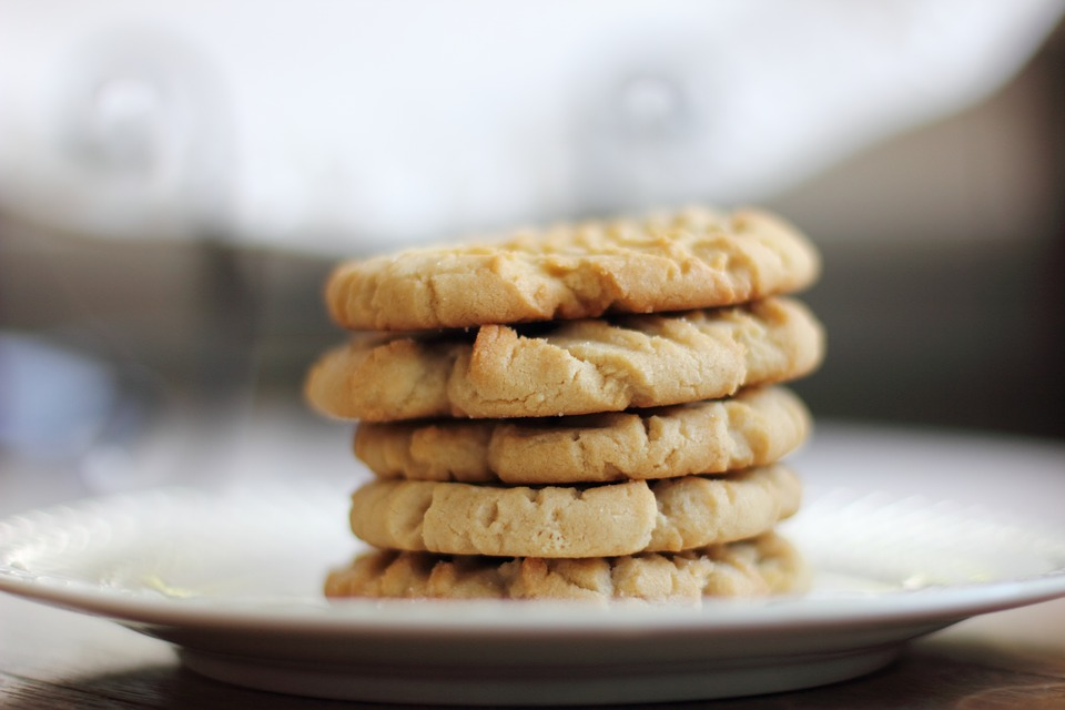 Pumpkin cookies stacked upon one another on a plate.