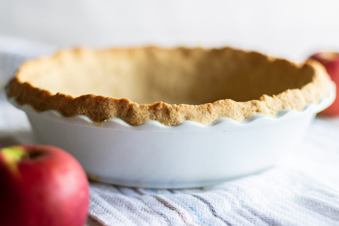 Pie crust in a bowl next to an apple.