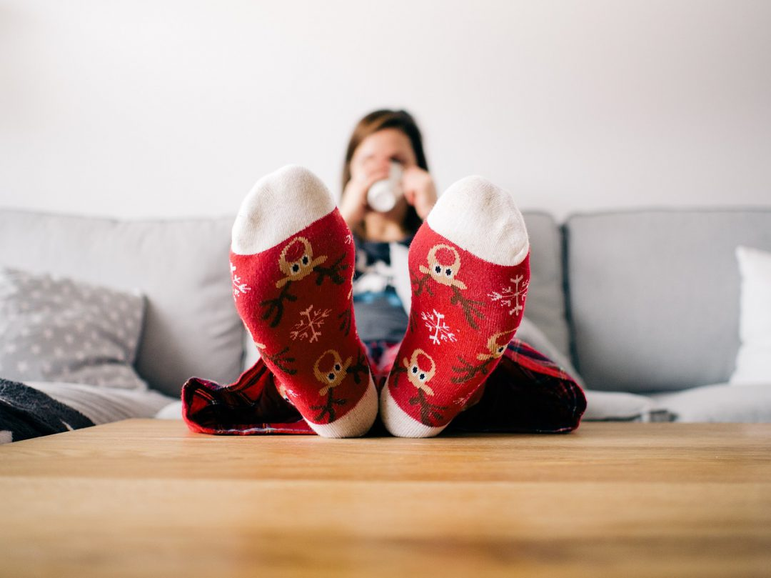 Woman sitting on a couch drinking out of a mug in holiday socks.