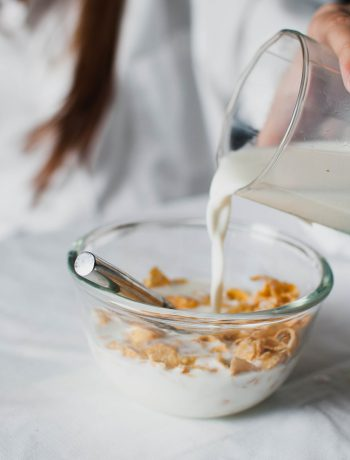 person pouring milk into bowl of cereal