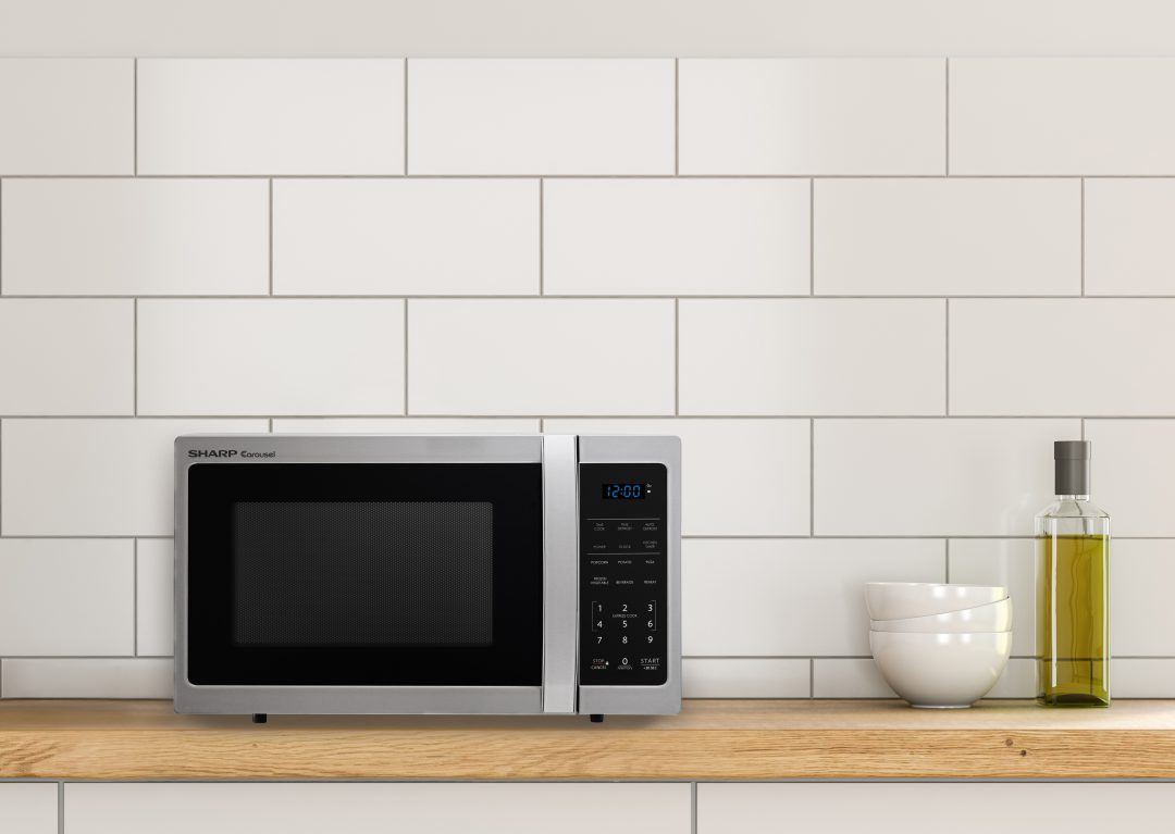 Sharp microwave on a countertop next to a bowl and a jar.