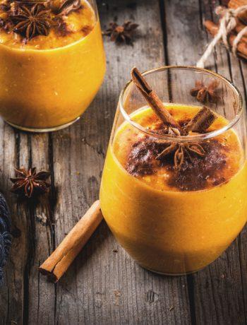 glass of pumpkin beverage with cinnamon sticks