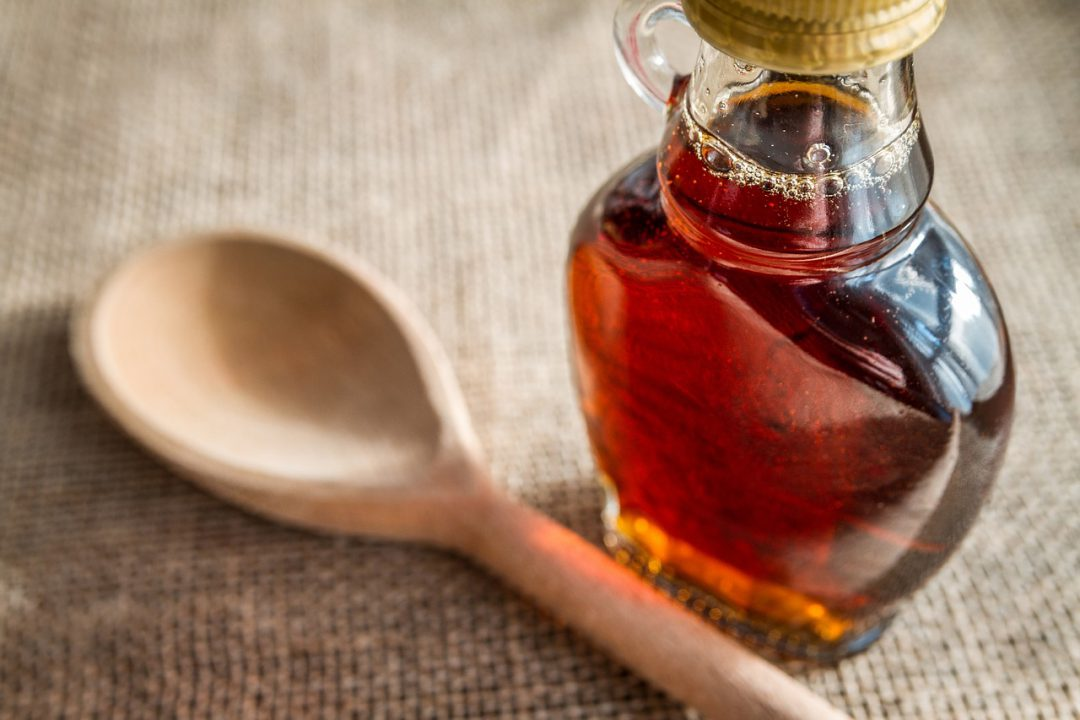 wooden spoon with a bottle of maple syrup