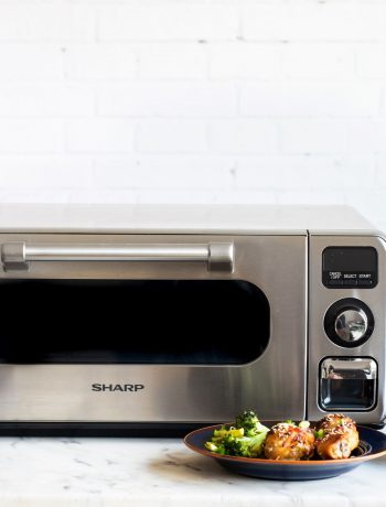 Sharp Superheated Steam Countertop Oven surrounded by plates of food