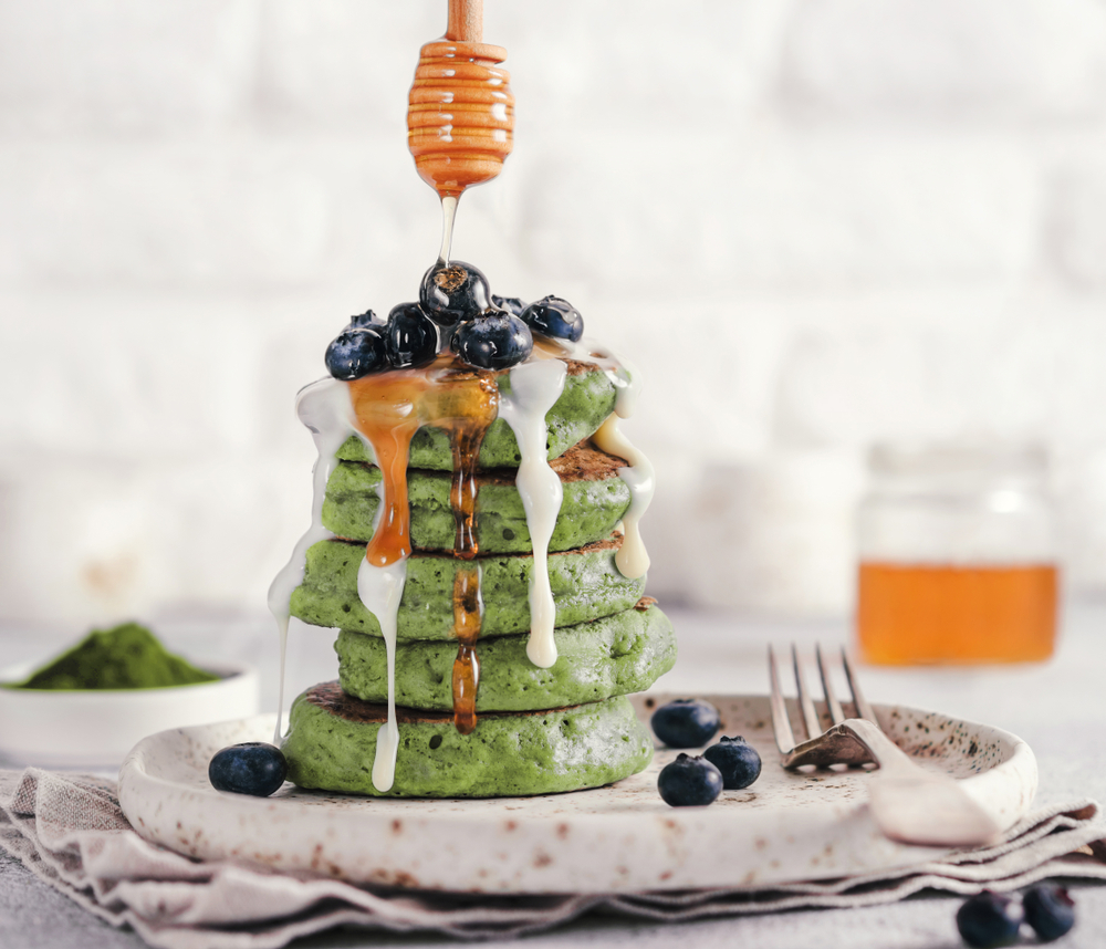 Matcha pancakes stacked on a plate with blueberries and syrup.