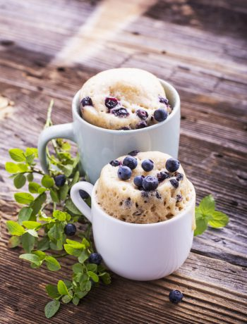 Two blueberry mug cakes sitting on a wooden table.