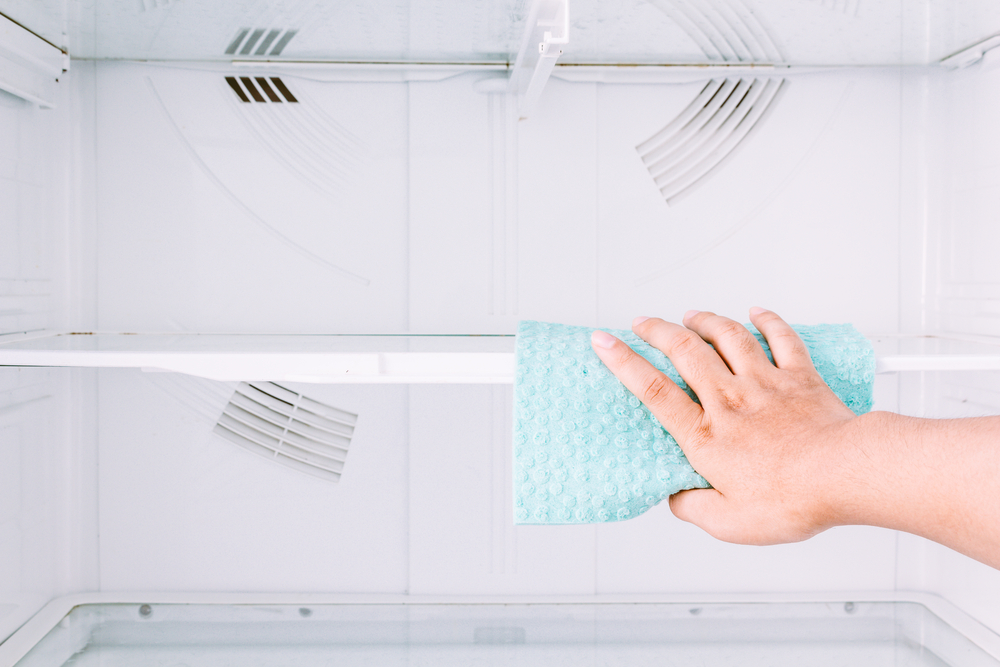Cleaning the shelves of a fridge with a blue cloth.