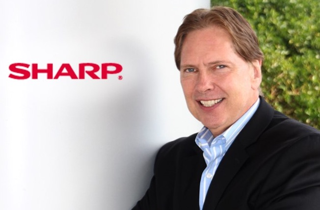 Senior Vice President Peter Weedfald in front of SHARP logo