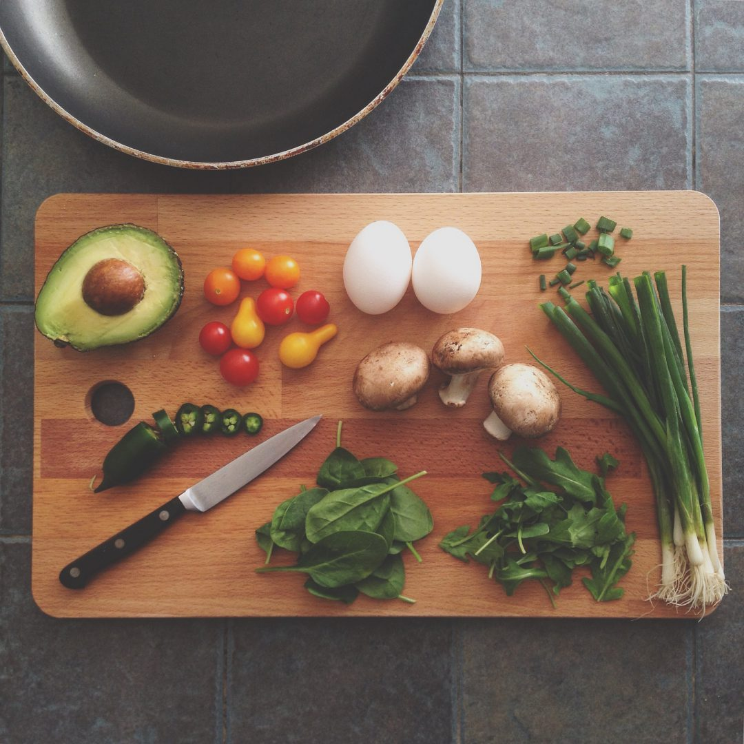 Meal prep with vegetables and a knife and cutting board.