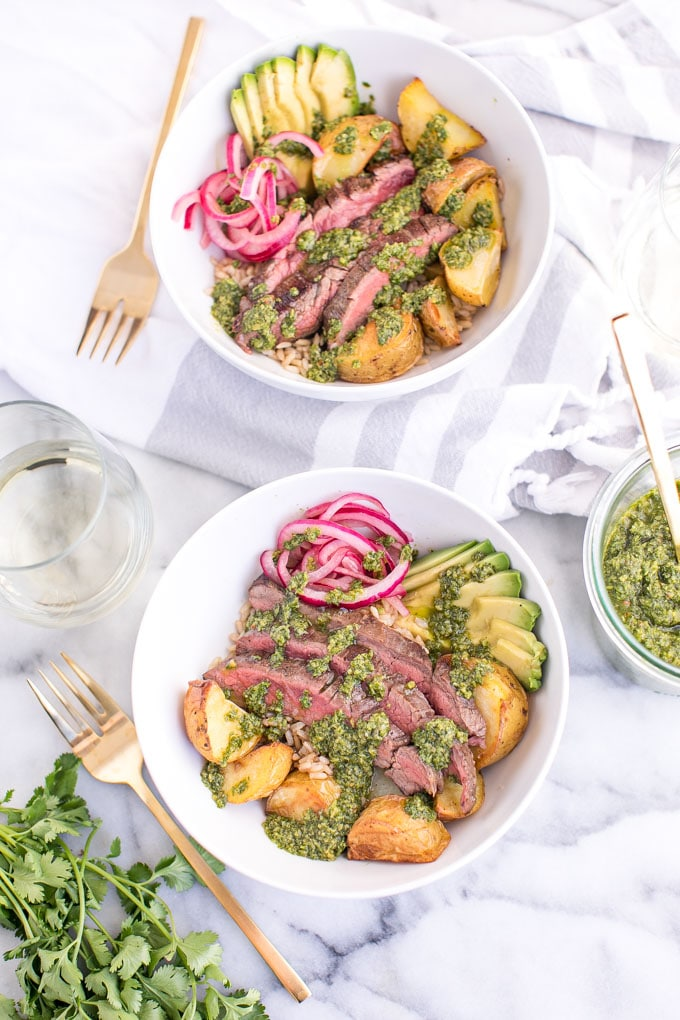 Chimichurri Steak Bowls with Roasted Potatoes in two bowls with forks
