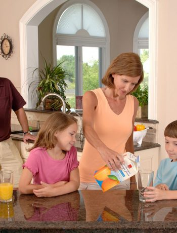 Family of four in a kitchen drinking orange juice