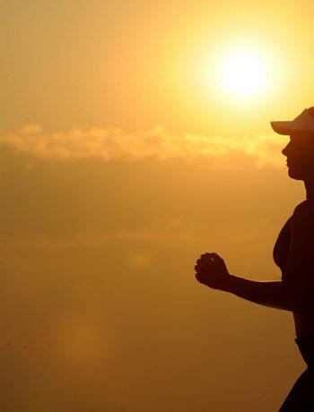 Woman jogging along a sunset