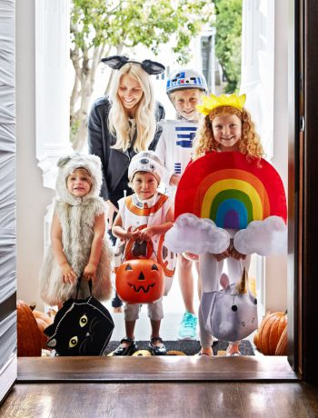 Family trick or treating at the doorstep.