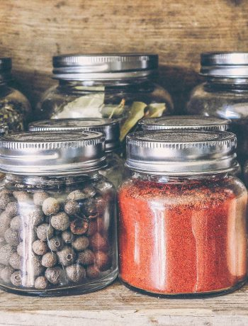 Mason jars in a wooden cabinet with fruits and ingredients.