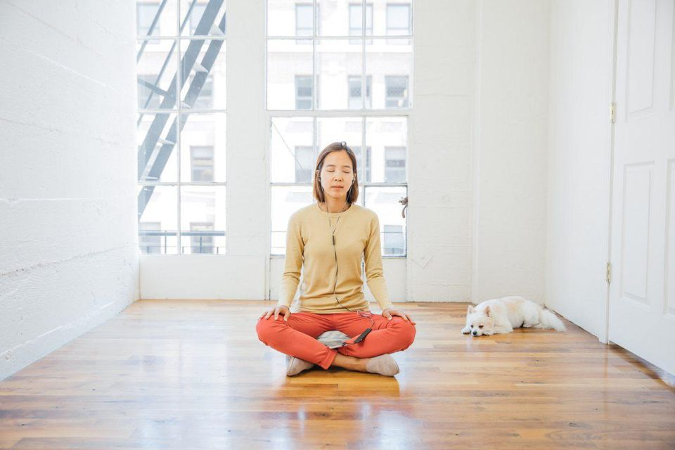 Woman practicing mindfulness in an urban apartment.