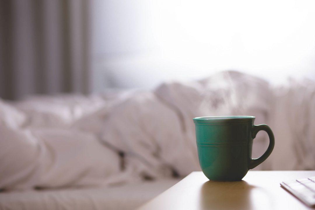 Mug of coffee next to bed.