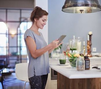 Woman in a kitchen looking up recipes on a tablet.