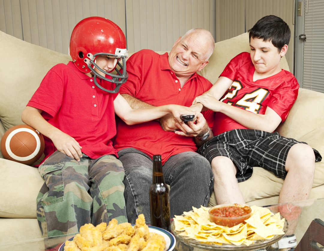 Two children fighting an adult over the remote.
