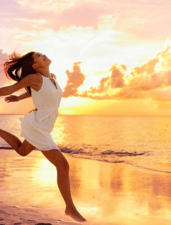 Woman running with joy across the ocean.