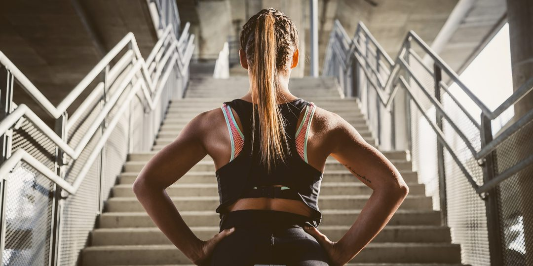 Woman preparing to exercise up the stairs.