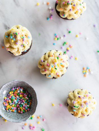 Cupcakes being prepared with sprinkles.
