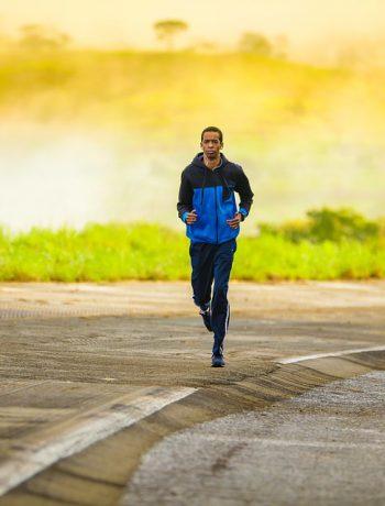 A man jogging alongside a highway.