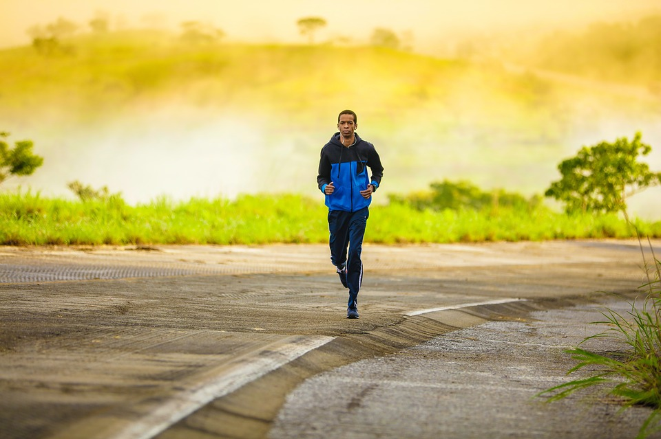 A man jogging alongside a highway.