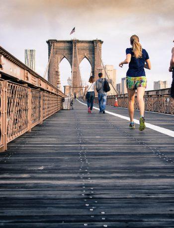 Joggers jogging across Brooklyn Bridge.
