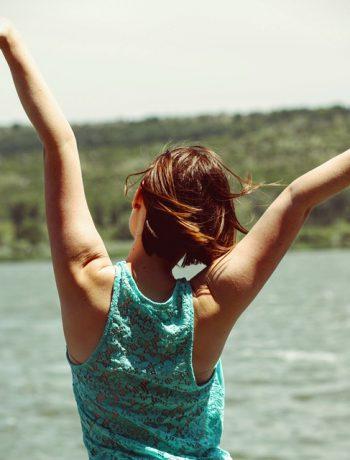 Woman expressing joy outside of lake.