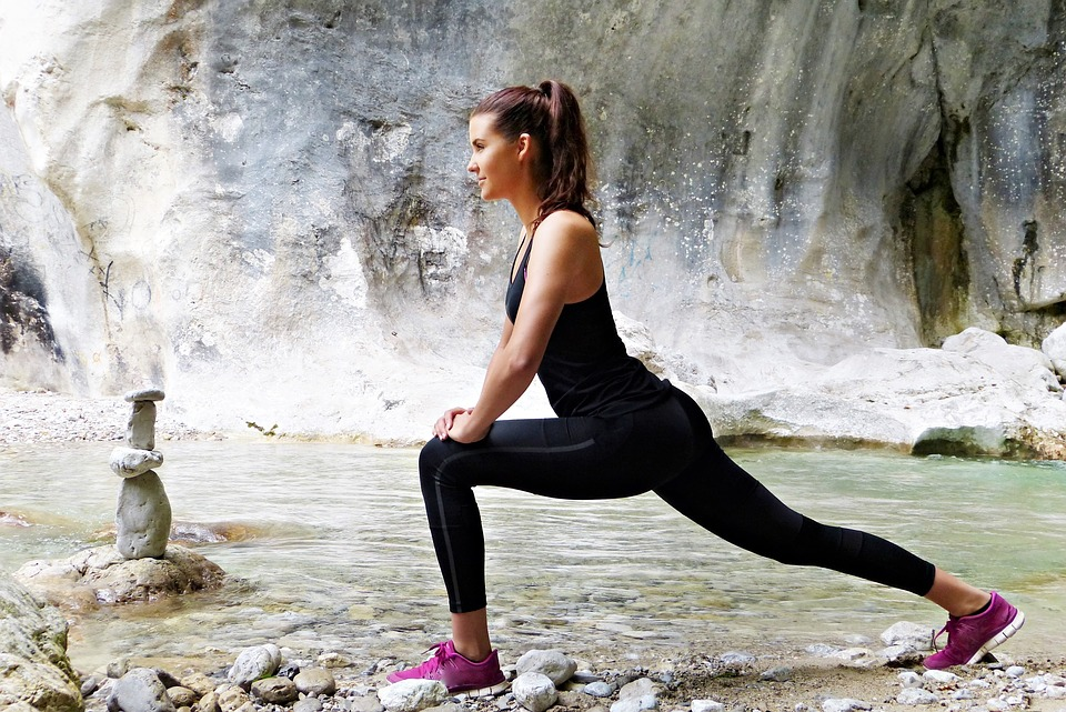 Woman stretching near a mountain.