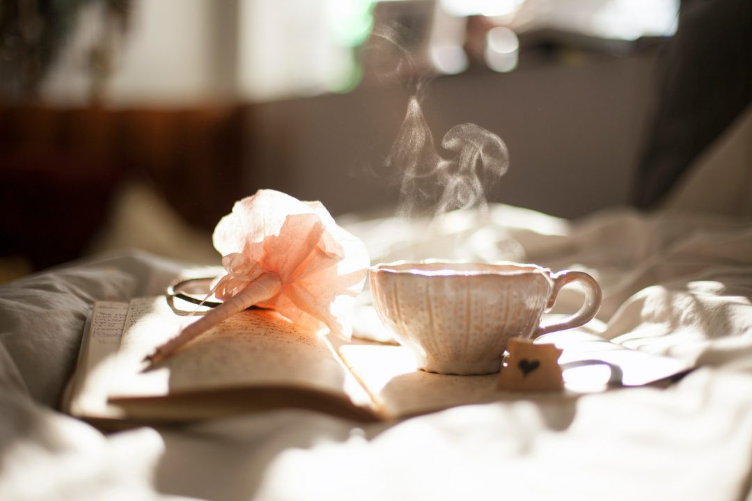 Tea, pen, and journal on a blanket.