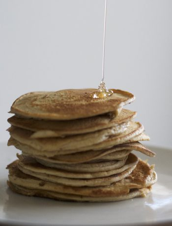 Pancakes being stacked with syrup.