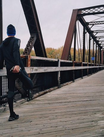 Jogger stretching to prepare to cross outdoor pedestrian bridge.