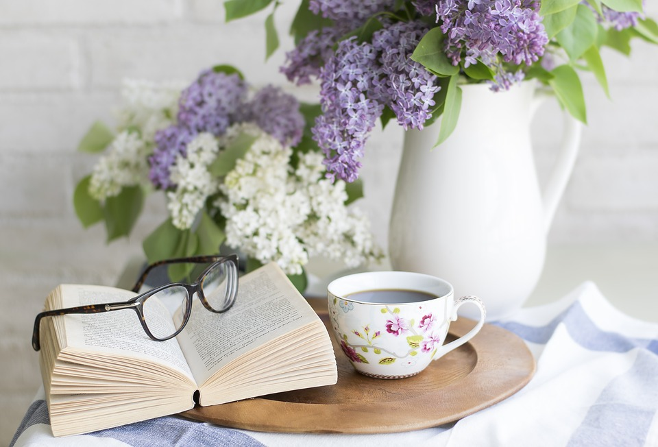 Floral arrangement next to a book and glasses.