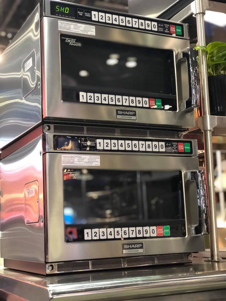 Commercial grade Sharp microwaves stacked upon one another.
