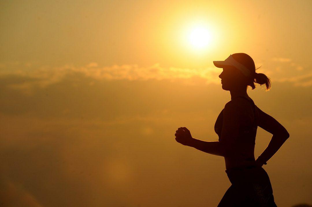 Woman jogging along a sunset.