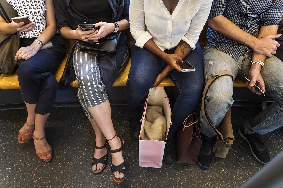 People using their smartphones using mass transportation.