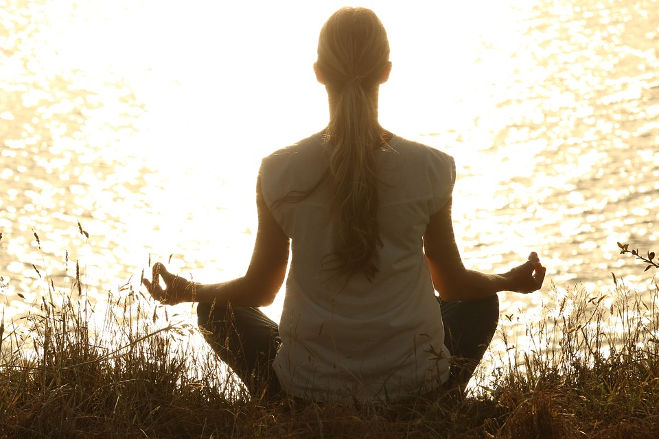 Woman meditating near a body of water.