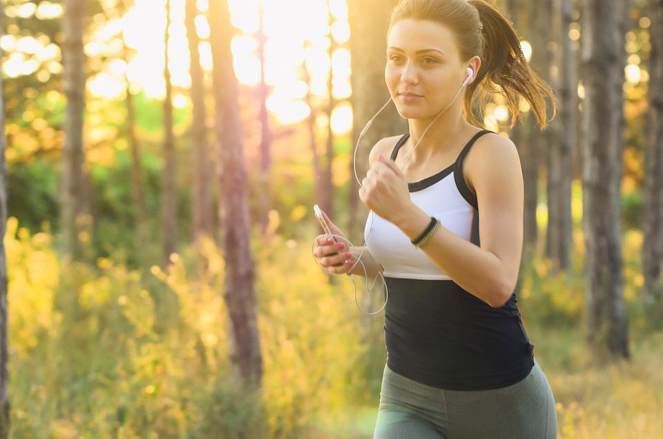 Woman jogging alongside the woods.