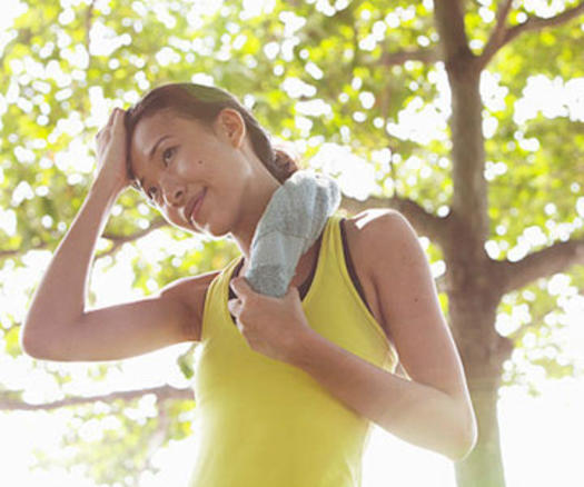 A woman exercising outdoors near a tree.