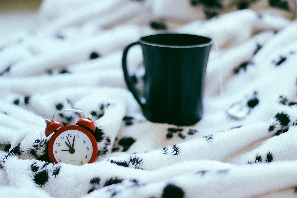 Black coffee mug on a blanket with clock.