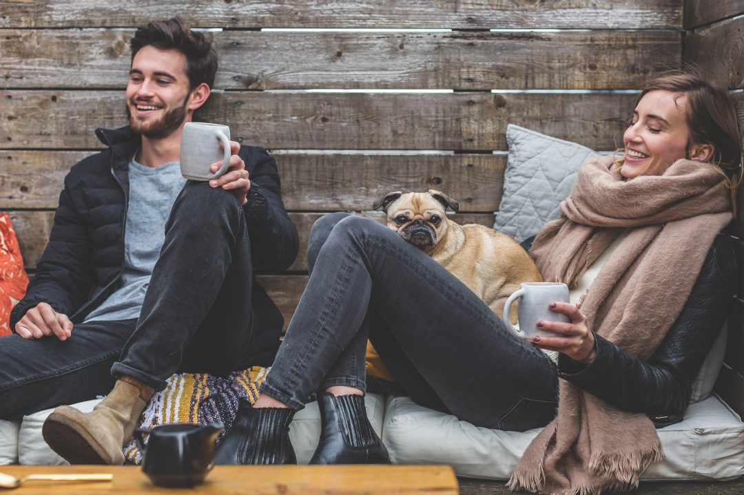 Two people sitting on a bench drinking from mugs next to their dogs.