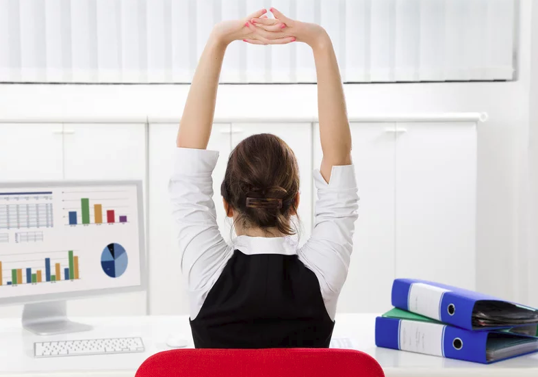 A woman sitting at her desk practicing different stretch techniques.