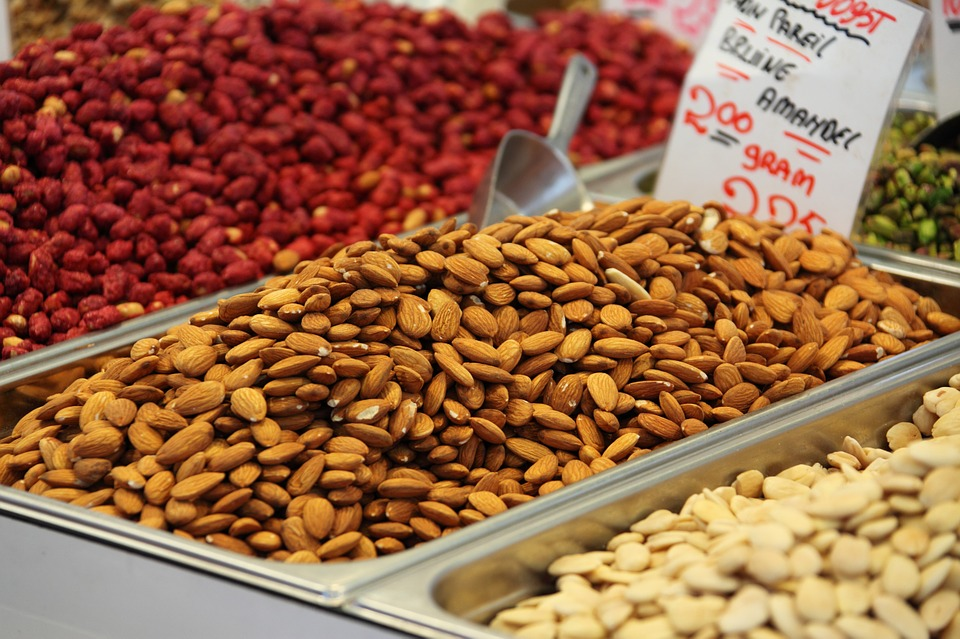An array of different nuts in a grocery store or market setting.