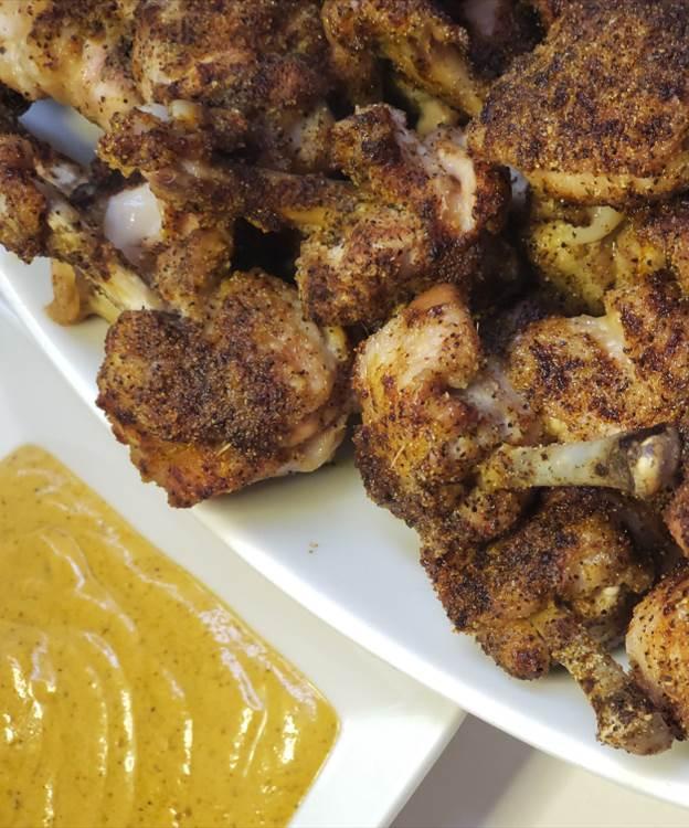 Chicken lollipops next to honey mustard dip.