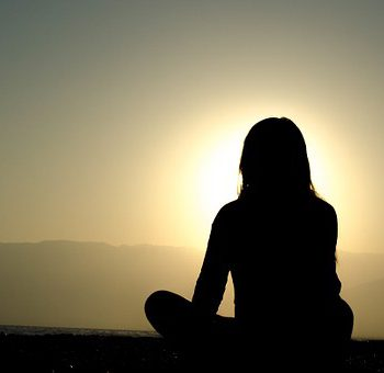 Woman meditating near sunrise.