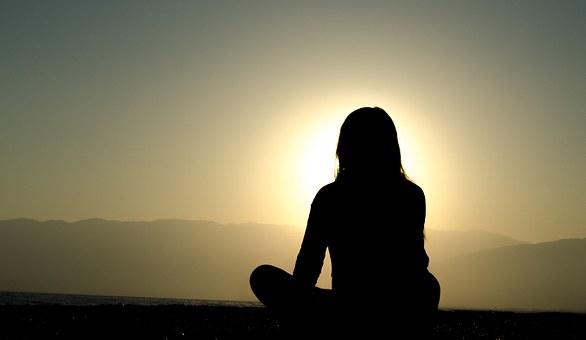 Woman meditating near sunrise.