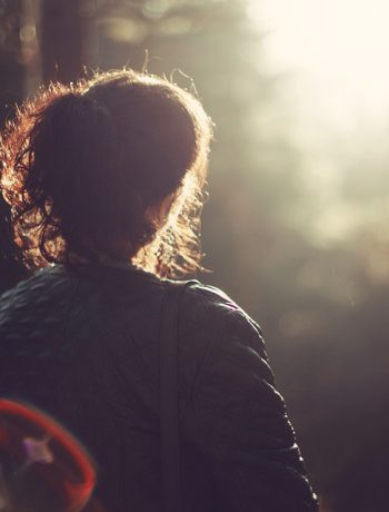 A woman staring into a wooded area with sunlight.